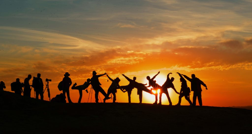 People posing in front of sunset
