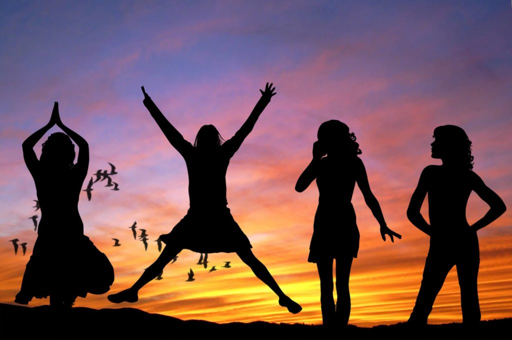 Four women dancing in front of a sunset